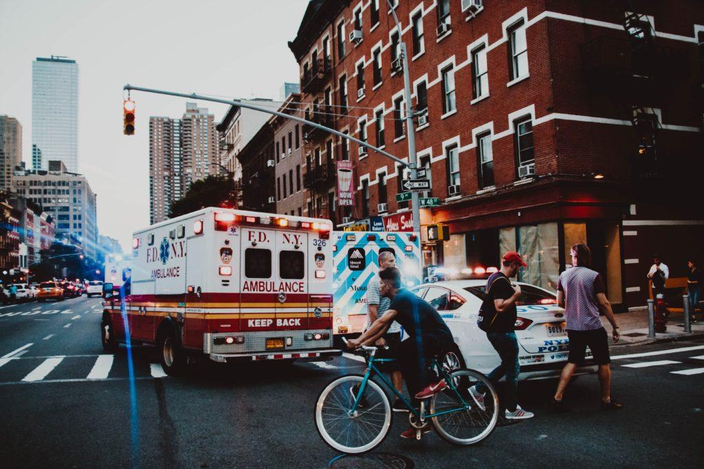 drei Personen, die in der Nähe eines Mannes gehen und Fahrrad fahren auf der Straße in der Nähe eines Krankenwagens.
