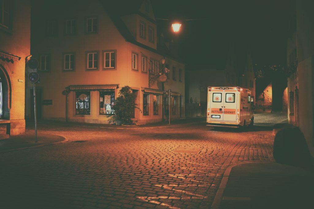 weißer und orangener Bus auf der Straße während der Nachtzeit